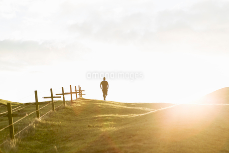 Distant view of man jogging on grassy field against sky during sunny dayの写真素材 [FYI02142733]