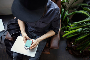 High angle view of blogger using phone while sitting on chairの写真素材 [FYI02142739]