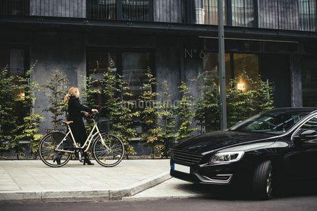 Full length side view of businesswoman with bicycle walking by buildingの写真素材 [FYI02142742]