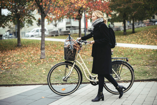 Full length side view of businesswoman with bicycle walking on footpath during autumnの写真素材 [FYI02142762]