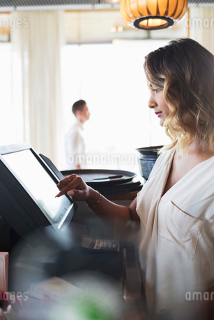 Side view of female owner touching cash register at restaurantの写真素材 [FYI02142777]