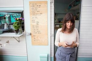 Female owner using smart phone outside food truckの写真素材 [FYI02142830]