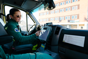 Side view of female paramedic touching screen on dashboard while driving ambulanceの写真素材 [FYI02142838]