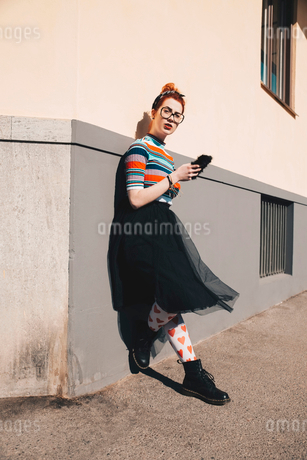 Full length of young woman using mobile phone while standing by wallの写真素材 [FYI02142873]