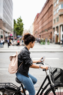 Woman looking at phone while riding bicycle on city streetの写真素材 [FYI02142898]