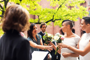 Lesbian couple giving flower bouquets to guest during wedding ceremonyの写真素材 [FYI02142913]