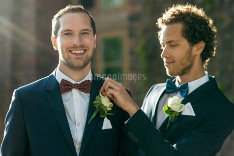 Portrait of happy man standing with gay partner adjusting boutonniereの写真素材 [FYI02142921]
