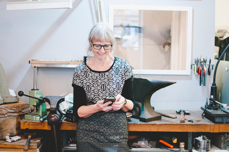 Smiling senior woman using smart phone in jewelry workshopの写真素材 [FYI02142969]