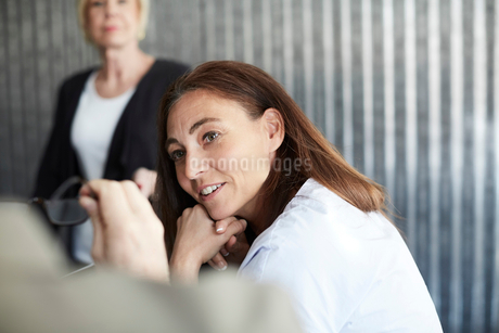 Mature female professional sitting with colleagues in board room during meetingの写真素材 [FYI02142970]