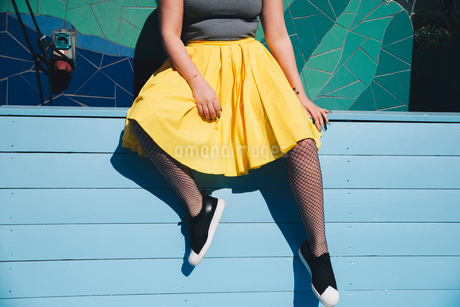 Low section of young woman sitting on bench against mosaic wallの写真素材 [FYI02142996]