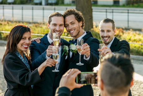 Happy friends with champagne flutes posing for photograph during wedding ceremonyの写真素材 [FYI02143000]