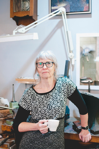 Portrait of confident senior woman holding coffee cup in jewelry shopの写真素材 [FYI02143006]