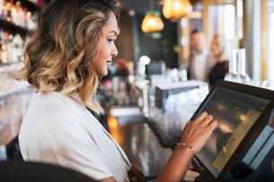 Side view of female owner using cash register at restaurantの写真素材 [FYI02143009]