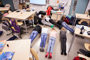 High angle view of junior high students in plank position at classroomの写真素材 [FYI02143010]