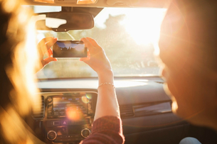 Man looking at woman photographing from mobile phone through car windshieldの写真素材 [FYI02143011]