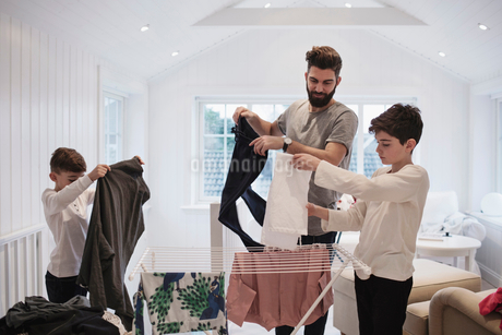 Father and boys drying clothes at homeの写真素材 [FYI02143036]