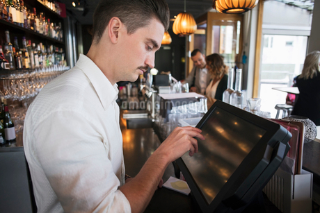Side view of male owner using cash register at checkout in restaurantの写真素材 [FYI02143039]