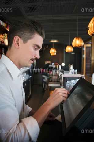 Side view of owner using cash register at checkout in restaurantの写真素材 [FYI02143078]