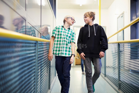 Boy talking with male friend while walking in school corridorの写真素材 [FYI02143117]