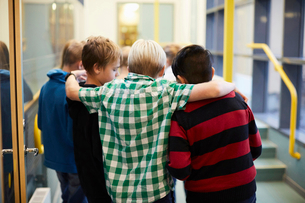 Boys standing arm around in school corridorの写真素材 [FYI02143149]