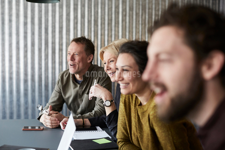Smiling creative business colleagues sitting at conference table while looking away in board roomの写真素材 [FYI02143211]
