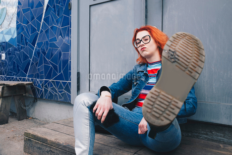 Redhead young woman kicking while sitting against door of buildingの写真素材 [FYI02143241]