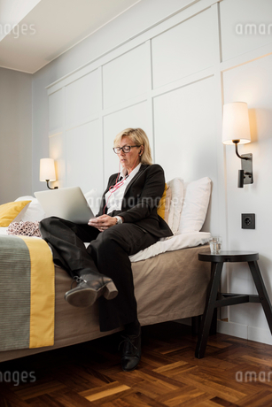 Businesswoman sitting on bed using laptop against wall in hotel roomの写真素材 [FYI02143307]