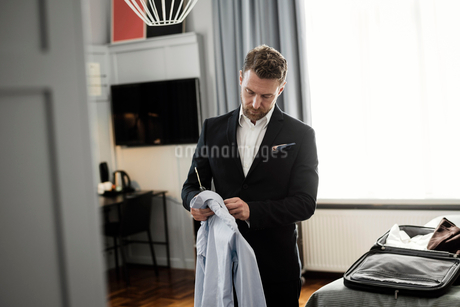 Mature man holding shirt in coathanger standing at hotel roomの写真素材 [FYI02143314]