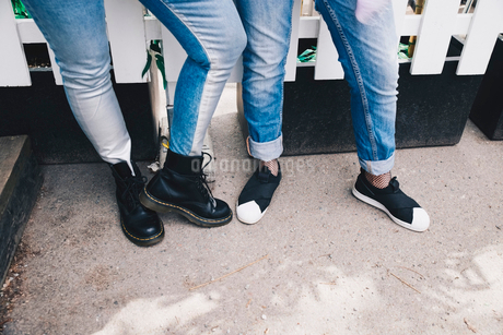 Low section of female friends wearing jeans while standing against fenceの写真素材 [FYI02143316]
