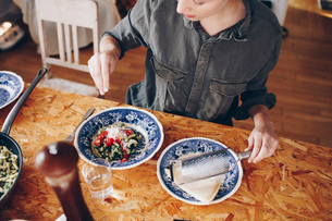High angle view of woman sprinkling cheese on pasta in plate at homeの写真素材 [FYI02143324]