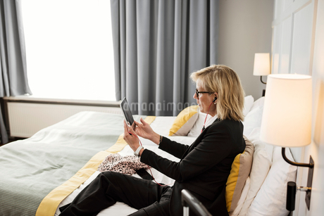 Side view of businesswoman using digital tablet sitting on bed at hotel roomの写真素材 [FYI02143340]