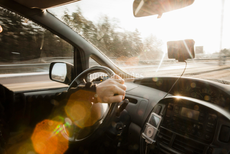 Cropped image of man driving car on sunny dayの写真素材 [FYI02143353]