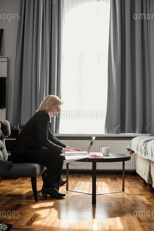Side view of mature businesswoman using laptop by window at hotel roomの写真素材 [FYI02143403]