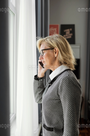 Side view of businesswoman listening to smart phone while looking through window at hotel roomの写真素材 [FYI02143405]