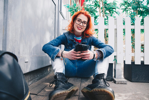 Portrait of redhead young woman using mobile phone while sitting by doorの写真素材 [FYI02143416]