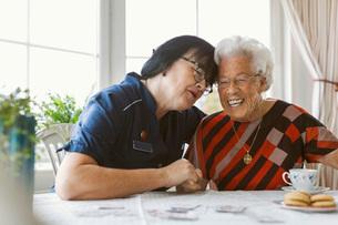 Happy caretaker and senior woman sitting at tableの写真素材 [FYI02143417]