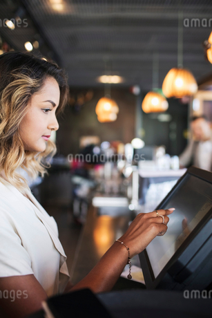 Side view of female owner touching cash register at checkout in restaurantの写真素材 [FYI02143439]