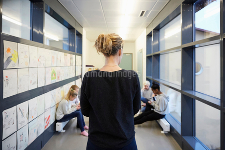 Rear view of teacher looking at students in school corridorの写真素材 [FYI02143450]