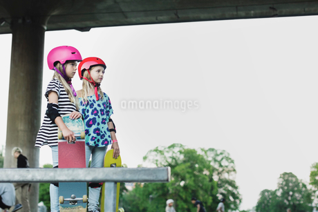 Friends wearing helmets holding skateboards while standing at park against clear skyの写真素材 [FYI02143472]