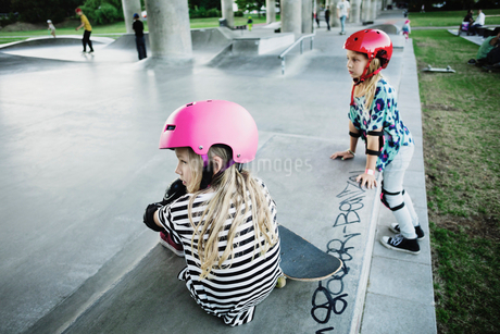 Friends looking away while resting at skateboard parkの写真素材 [FYI02143489]