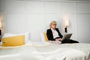 Mature businesswoman sitting on bed using laptop against wall at hotel roomの写真素材 [FYI02143498]