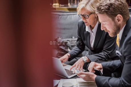 Business people using laptop and mobile phone during meeting in hotel receptionの写真素材 [FYI02143516]
