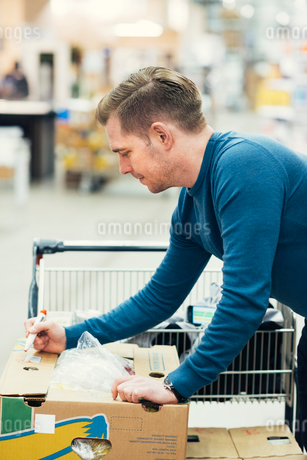 Side view of owner writing with felt tip pen on cardboard box at supermarketの写真素材 [FYI02143580]