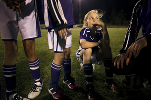 Girl looking at coach explaining strategy on soccer field at nightの写真素材 [FYI02143620]