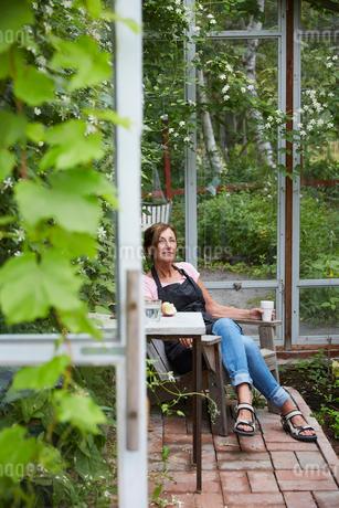 Female gardener resting in glass houseの写真素材 [FYI02143629]