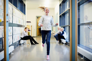 Smiling girl running in school corridor with friends in backgroundの写真素材 [FYI02143637]