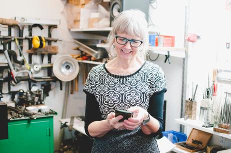 Smiling senior woman using mobile phone in jewelry workshopの写真素材 [FYI02143669]