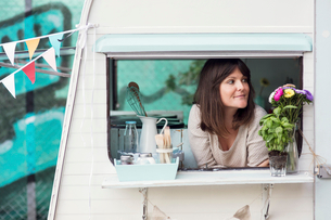 Thoughtful female owner looking out through food truck windowの写真素材 [FYI02143674]