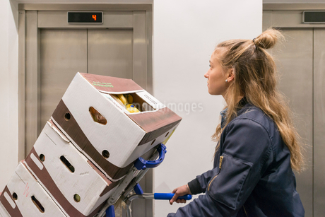 Side view of female worker pushing cardboard box stack on hand truck against escalator at supermarkeの写真素材 [FYI02143677]