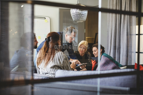 Businessman showing digital tablet to colleagues in board room during meeting seen from glassの写真素材 [FYI02143693]